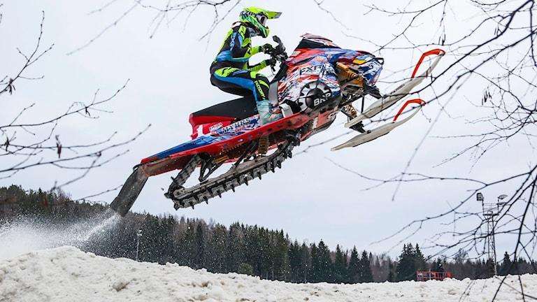 Skotercrossförare hoppar med sin snöskoter på tävlingsbana