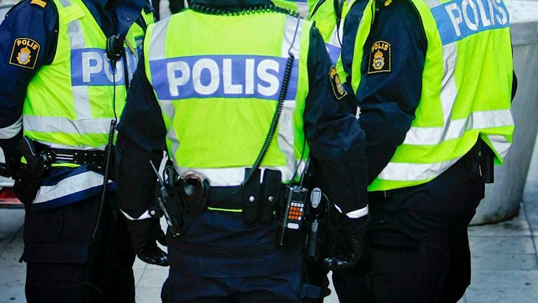 Ryggen på tre poliser