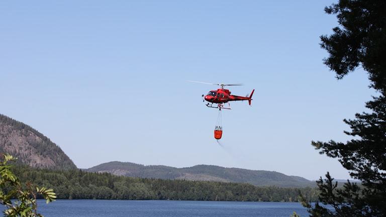 Bild av röd helikopter mot blå himmelbakgrund