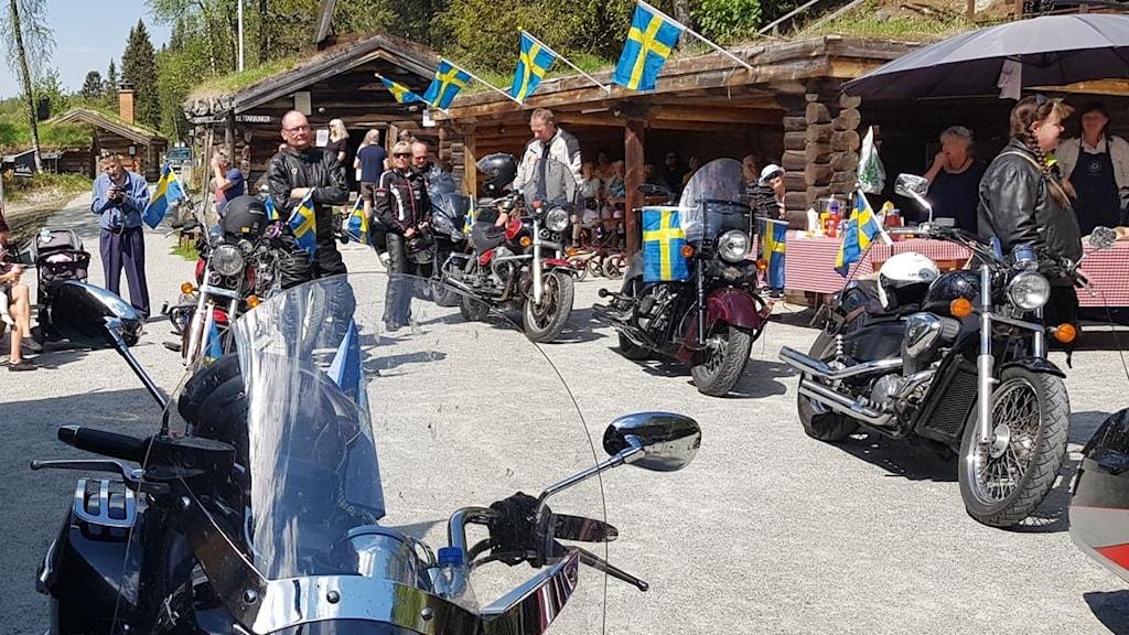 Motorcyklister bland marknadsbodar prydda med svenska flaggor en solig sommardag