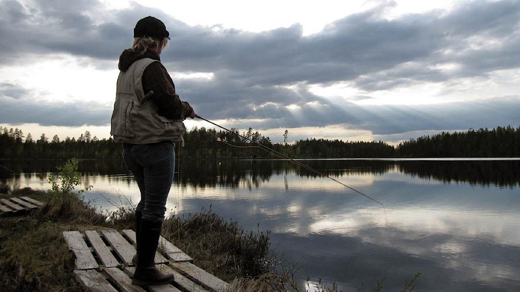 En kvinna står och fiskar