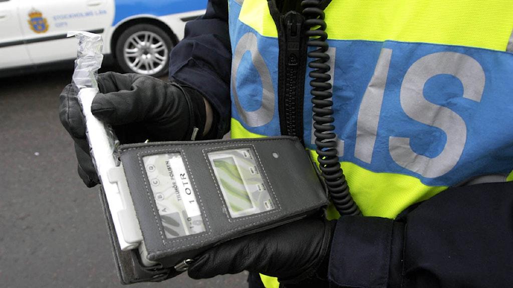 Polisen kontrollerar en alkoholmätare