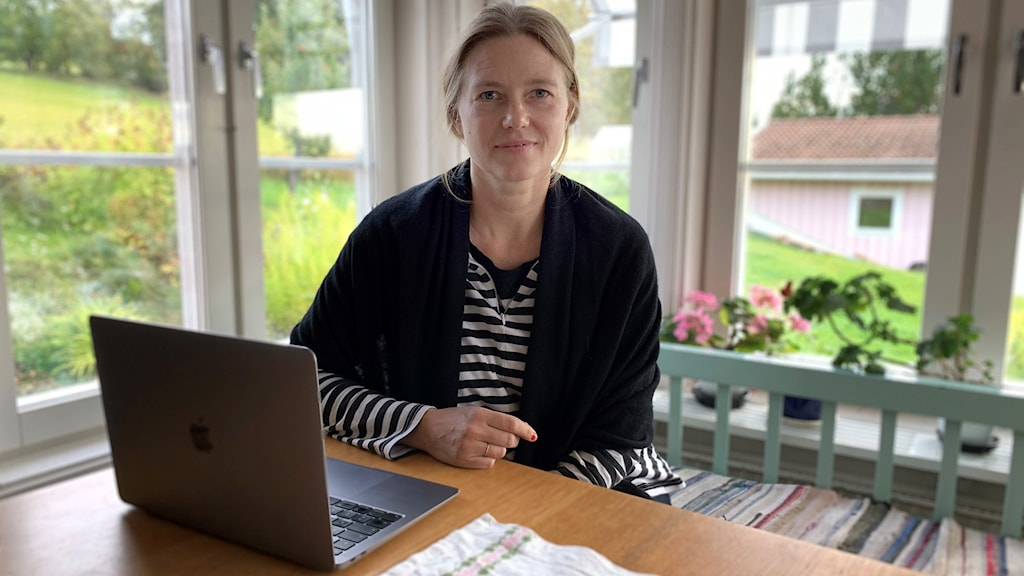En kvinna sitter på en grön träsoffa vid ett köksbord. På bordet står en bärbar dator.