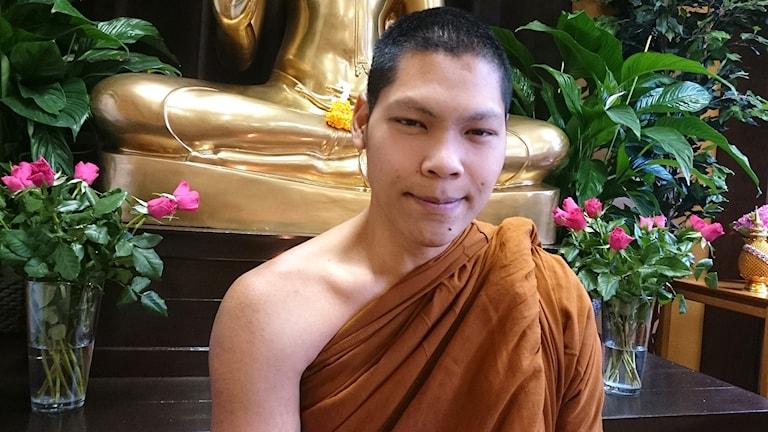 buddhistisk munk vid altare