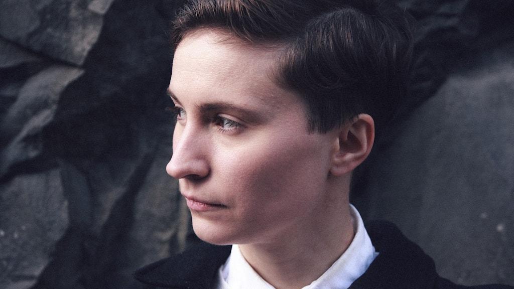Porträttbild allvarlig ung kvinna med kortklippt, brunt hår