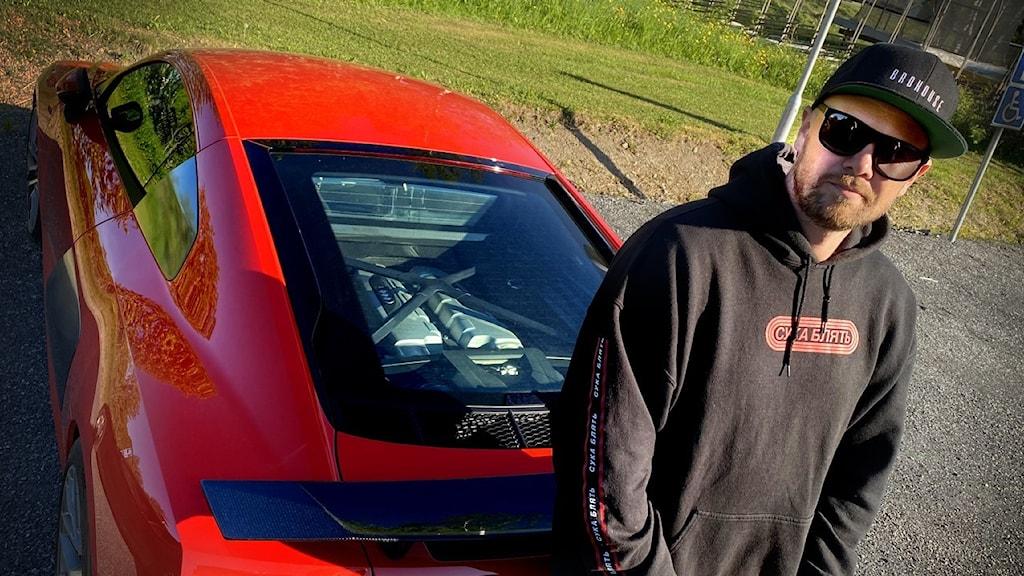 Man med keps och solglasögon bredvid röd sportbil.