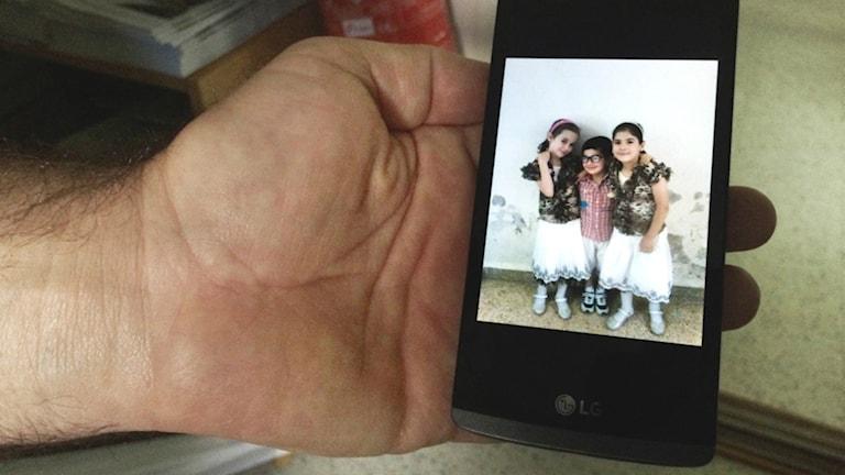 En mobilbild på tre barn
