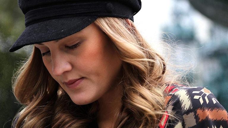 kvinna med långt blont hår och svart keps