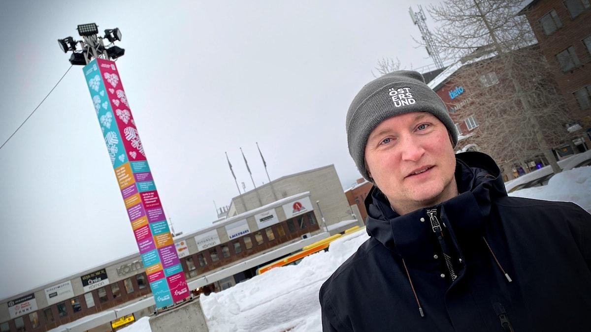 Man i vinterkläder i framför byggnader i Östersunds centrum.
