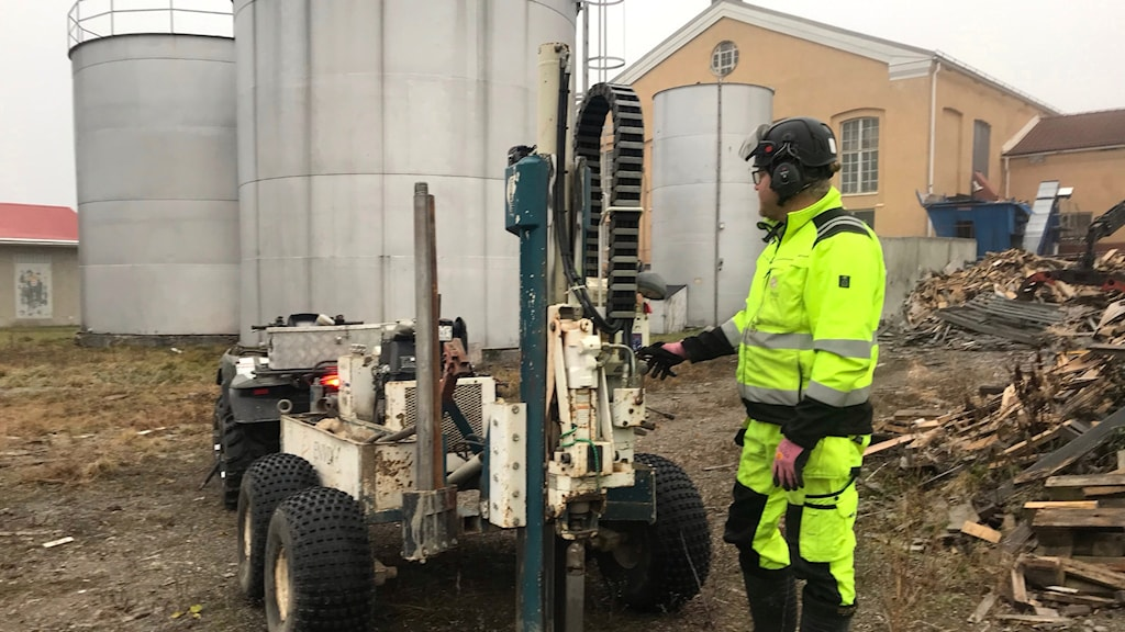 Man i reflexgula arbetskläder vid maskin på hjul som borrar i marken på fabriksområde med stora cisterner