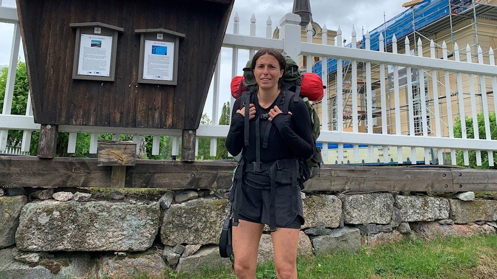 En kvinna med ryggsäck framför ett staket. I bakgrundens syns en kyrka,