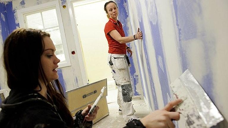 Två tjejer spacklar en vägg