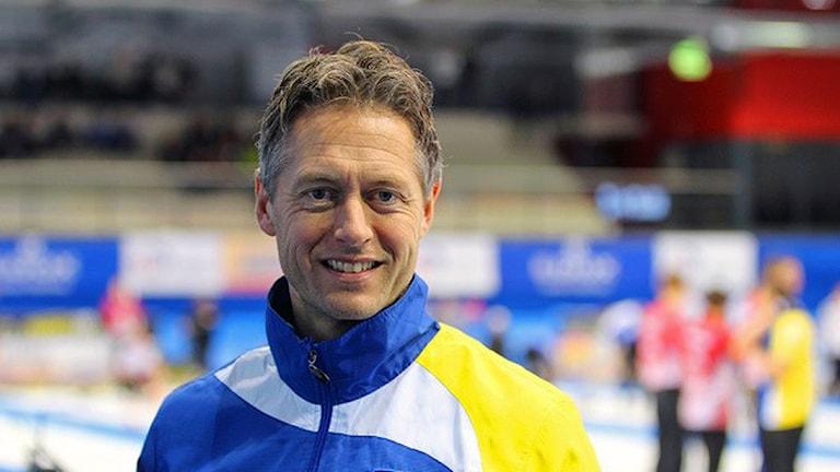 Peja Lindholm , man med träningsoverall står vid curlinghall