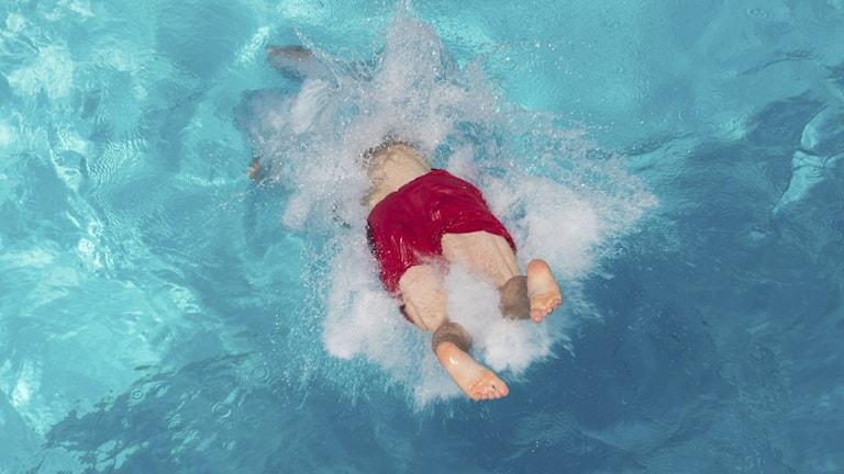Pojke dyker i badbassäng