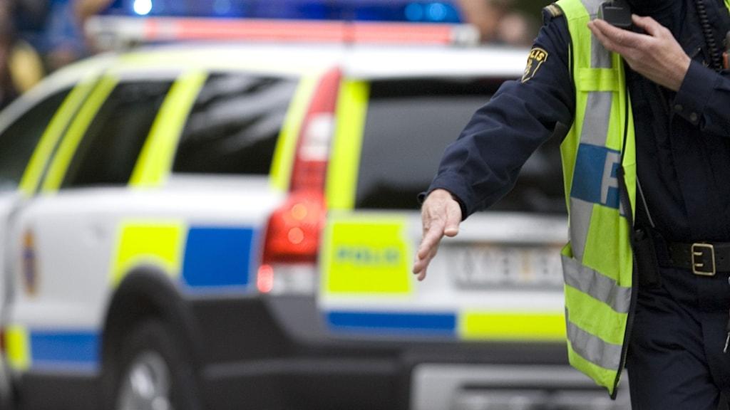Polisman vid polisbil längs väg
