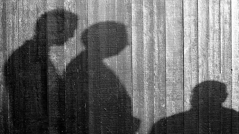 Skugga över två personer som tittar ner mot en tredje. Foto Janne Mårdberg/Sveriges Radio