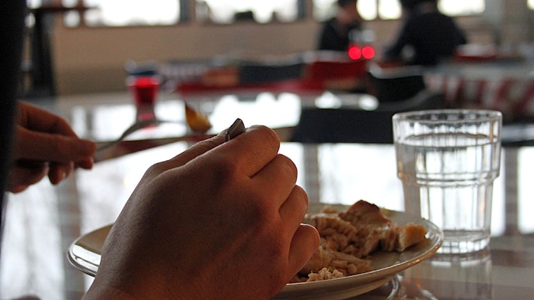 En person i lunchmatsalen sitter för sig själv och äter. Foto: Janne Mårdberg/Sveriges Radio