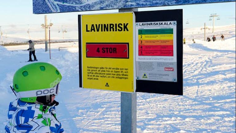 Skidåkare läser på skylt om lavinfara