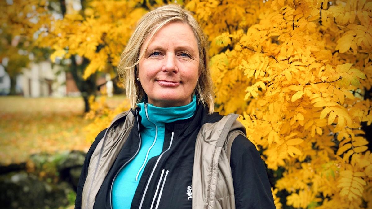 En blond kvinna framför gula rönnblad