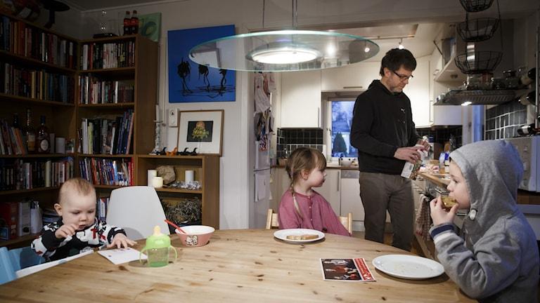 Tre barn sitter vid ett köksbord. I köket står en man och diskar.