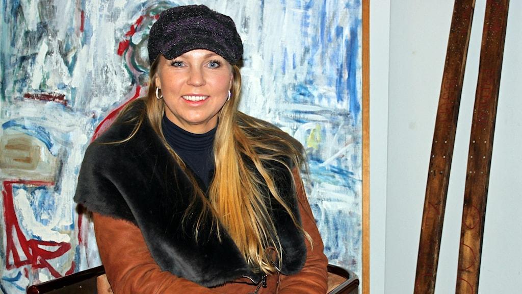 Blond leende kvinna i keps och skinnjacka sitter i en fåtölj