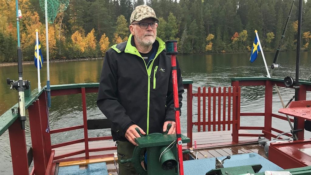 En äldre man på en hembyggd flotte på en sjö