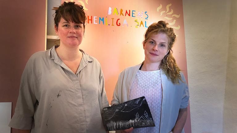 Två tjejer visar upp en teckning som ingår i en utställning