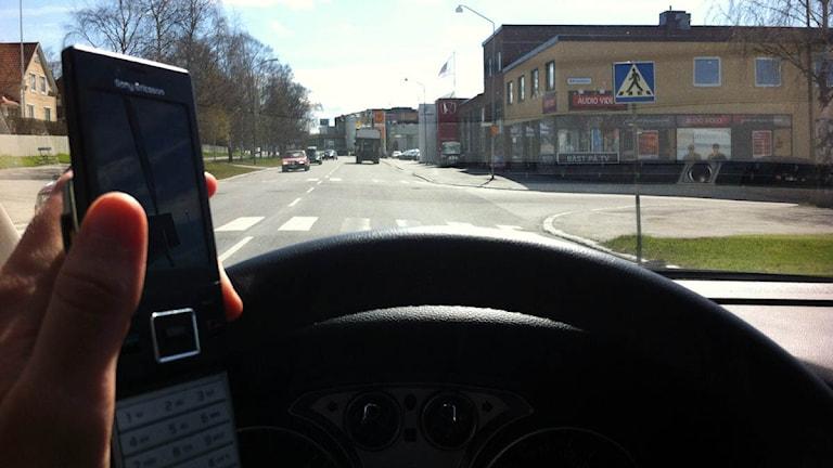 En bilförare håller i en mobiltelefon och bilratten