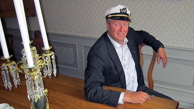 man i kostym och skepparmössa, sitter vid bord