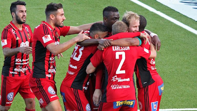 Fotbollsspelare i röda dräkter kramar om varandra efter ett mål