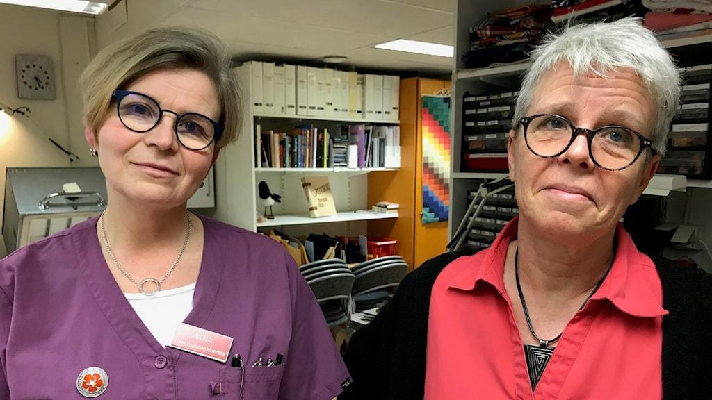 Två kvinnor med glasögon klädda i lila och röda sjukhuskläder.