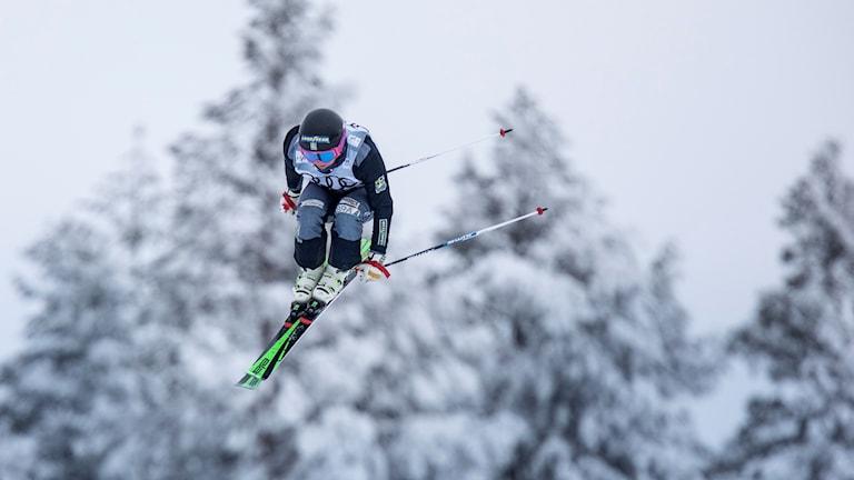Skicrossåkare hoppar i luften i snöig omgivning