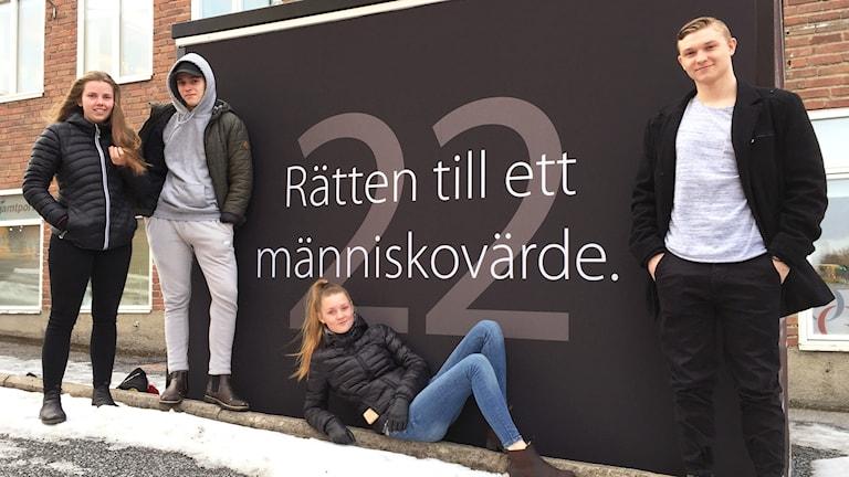 """Fyra personer står vid en svart container med texten """"Rätten till ett människovärde"""""""
