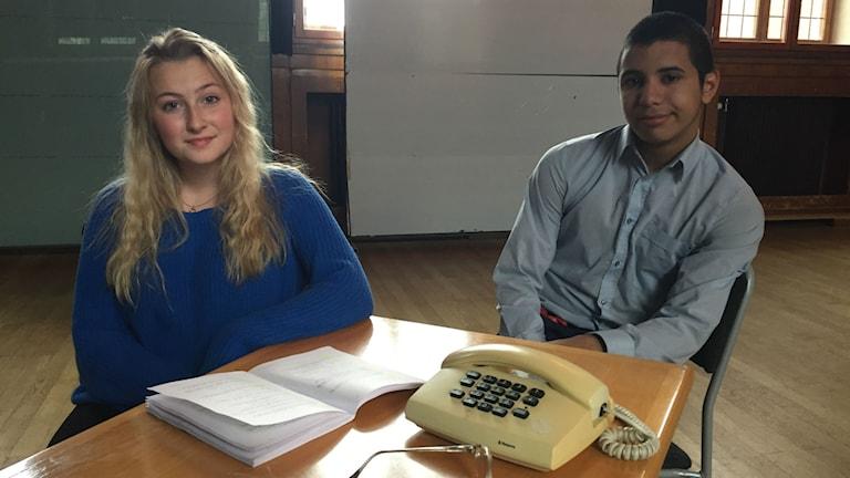 En tjej och en kille sitter vid ett bord.