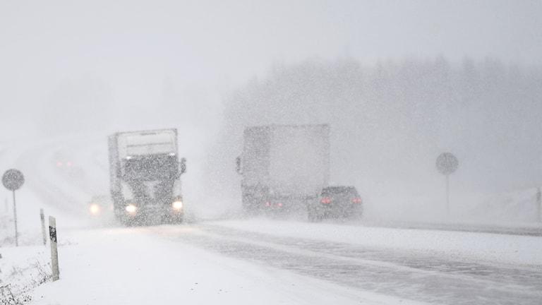 Personbilar och lastbilar kör på landsväg i ymnigt snöfall