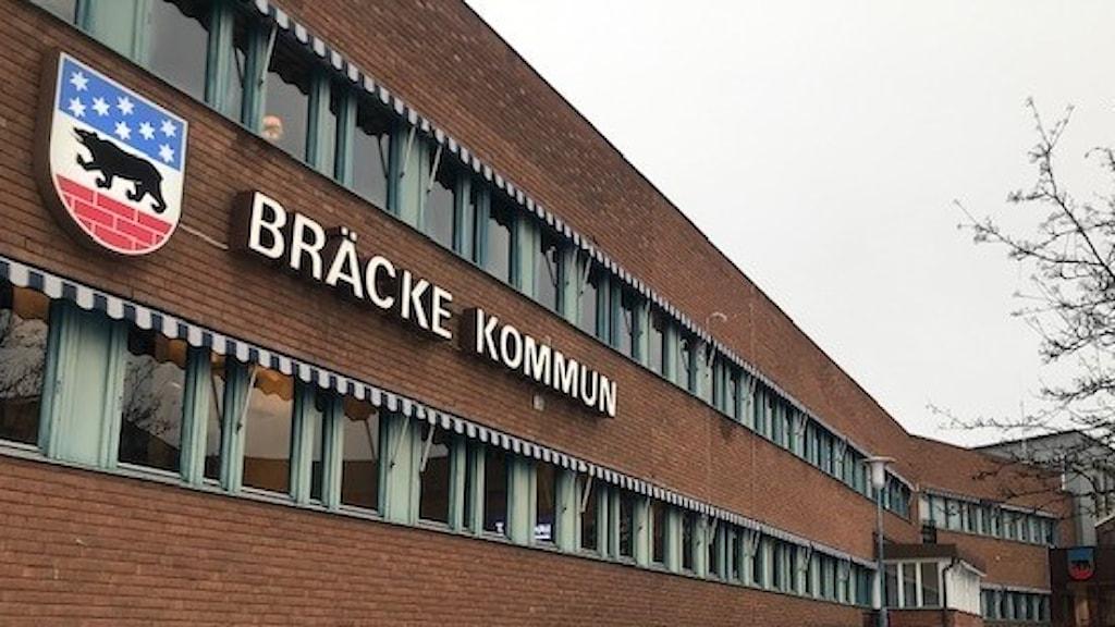 """Rödtegelbyggnad i två våningar med fasadskylt """"Bräcke kommun"""" och kommunemblem"""