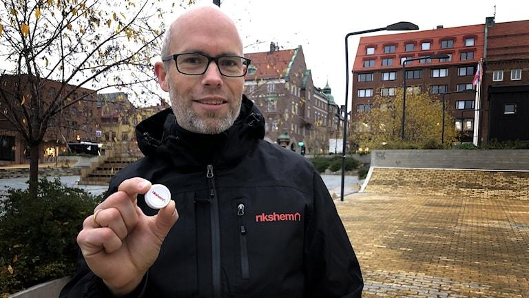 En man håller upp en vit, rund knapp.