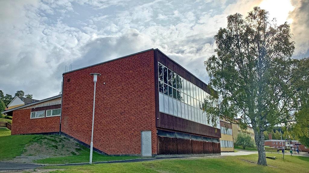En tegelbyggnad med en sida som är täckt av fönster.