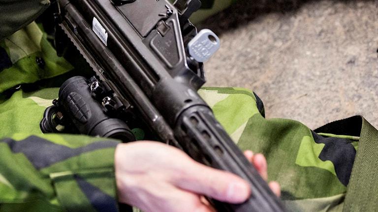 K-pist i knät på en kamoflageklädd soldat.