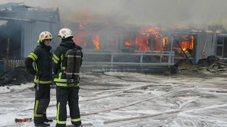 Två brandmän står och pratar framför ett hus som står i lågor.