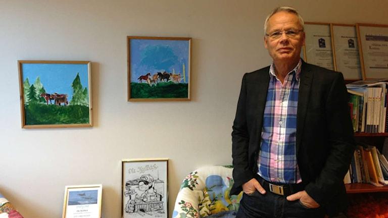 Ljushårig man i kavaj och rutig skjorta står framför en vägg med två tavlor och en bokhylla. Foto: Privat, Ola Skyllbäck