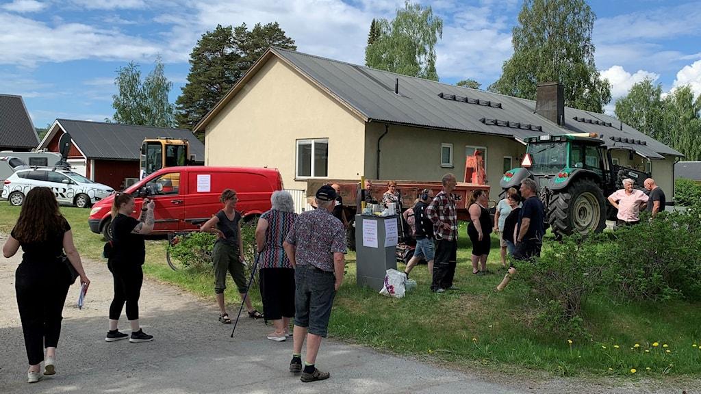 Personer som samlats framför ett hus och en traktor och flera bilar står framför huset.