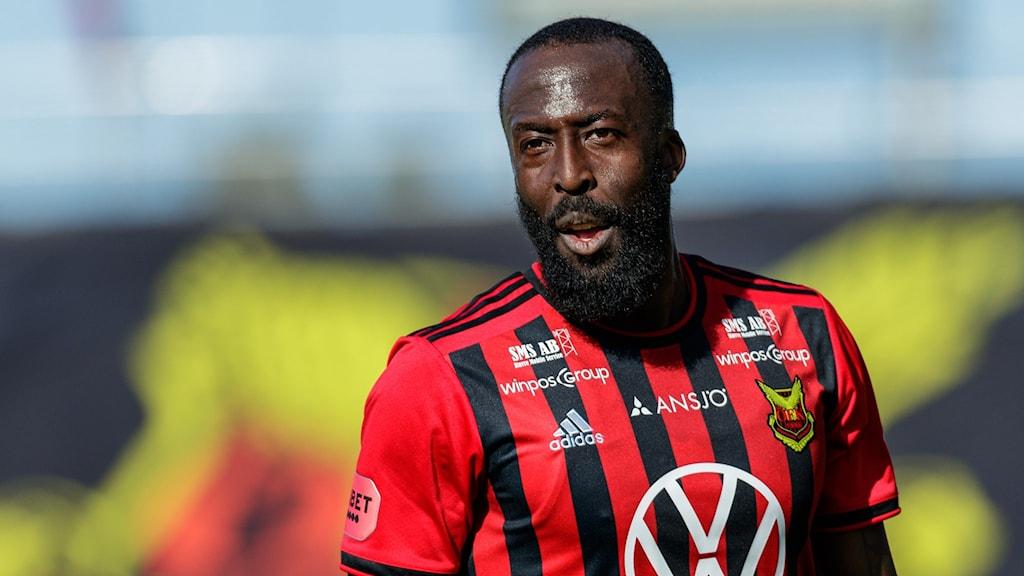 Man med mörk hy och skägg i röd-svartrandig fotbollströja