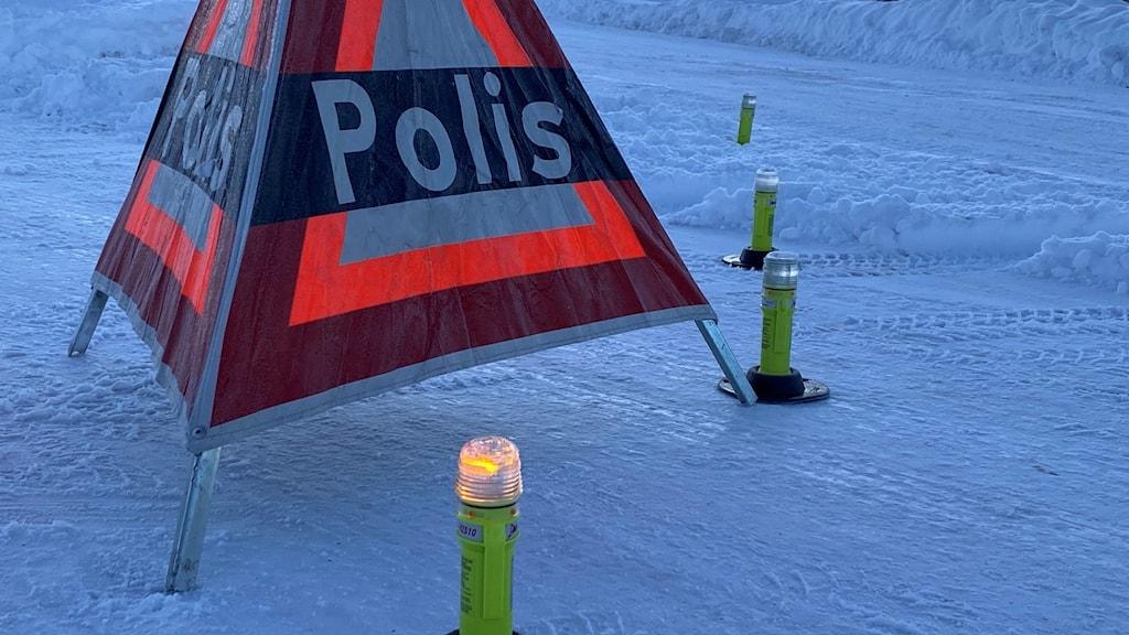 En varningstriangel som står på en snöklädd väg.