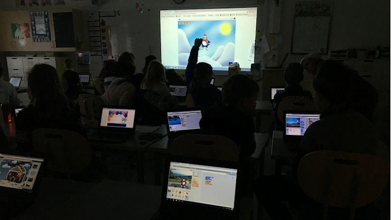 Skolklass sitter framför skärmar med animerat spel