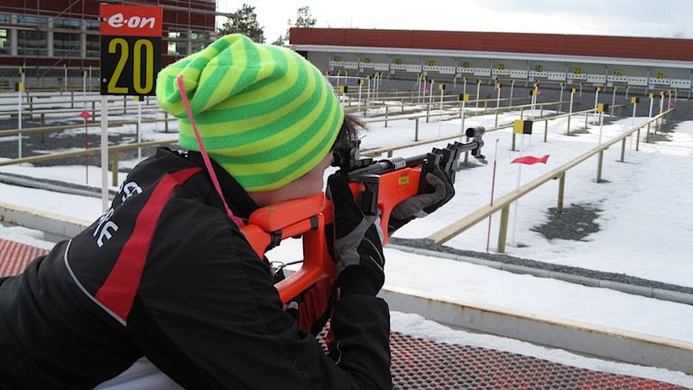 Pojke ligger ner och övar skytte på skidskyttestadion i Östersund. Skidskytteklubben Tullus SG har omkring 55 barn och ungdomar som tränar skidskytte, fler står på kö men klubben har svårt att ta emot fler barn, varken träningsutrymmet eller vapnen räcker till. Foto: Jessica Brander/Sveriges Radio