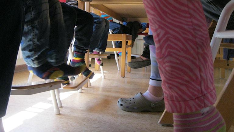 Bilden är tagen under ett matbord på en förskola. Den föreställer ben och fötter på flera barn och en pedagog.