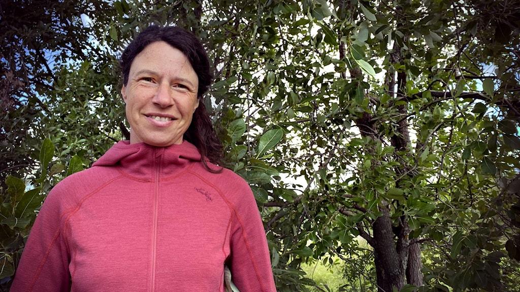 Kvinna i friluftskläder framför gröna lövträd.