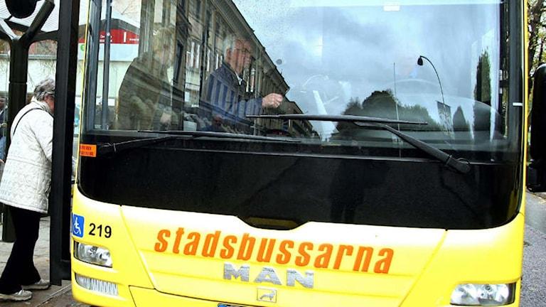 Resenärer kliver på en stadsbuss.