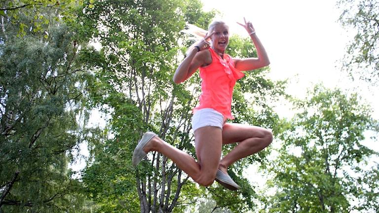 kvinna i rosa linne och vita shorts hoppar